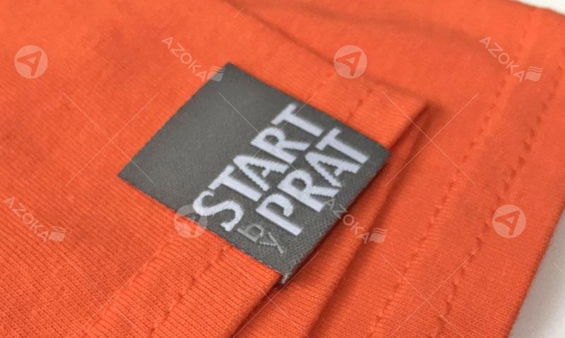 Mác dệt vải quần áo Start of Prat do Azoka thiết kế và in ấn